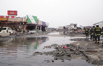 写真上:浸水した町の中、救助に向かう隊員 写真下:相次いで倒壊した建物が見られた(上下ともに宮城県気仙沼市のようす 東京消防庁 写真提供)