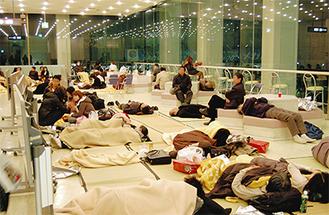 町田市民ホールで一時待機する帰宅困難者(12日午前0時30分ごろ撮影) 町田市内では10万件以上が停電し、壁の一部破損などの被害が報告されている