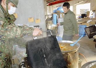 現地で自衛隊の炊き出しの手伝いをする共働学舎の職員(提供写真)