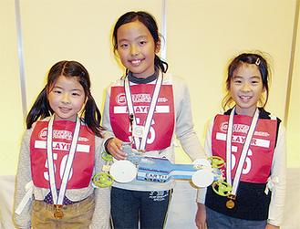 金メダルを受賞し、「アース号」を持つ工藤さん(中央)、山内さん(左)、草部さん