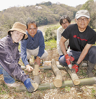 シイタケの原木作りをする新規就農者のみなさん(小野路町=13日撮影)