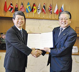 締結後、握手する石阪丈一市長(右)と酒井勲頭取