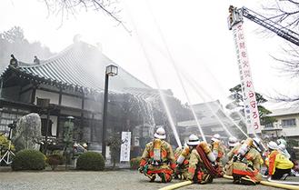 本堂に一斉放水する消防隊員ら