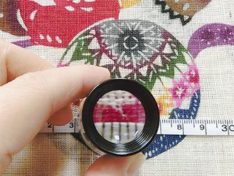 ルーペを使い作品を調査する。どのように織られているか、染色のぐあい、素材は何かなど、一瞬のチャンスをものにして調べまくる=写真の作品は沖縄の伝統的な紅型という染物