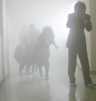煙が充満し視界が悪い廊下を避難する生徒たち