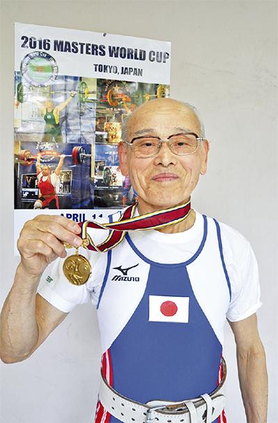 ユニフォームを着用し金メダルを掲げる水村さん(25日・トレーニングする総合体育館で)