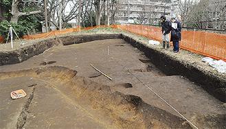 2人が覗いているのが住居跡(4分の1)。柵の右側がグランベリーモール跡地(3月1日)