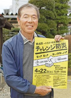 ポスターを掲げる実行委員長の小泉渉さん