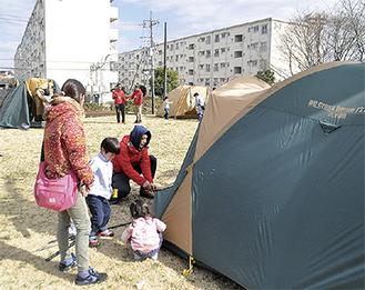 宿泊するためのテントを張る参加者ら(10日、町田山崎団地)