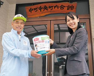 職員から回収ボックスを手渡される新井邦夫会長(左)