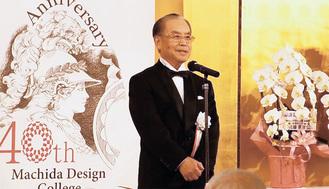 40周年ロゴの前であいさつする井上理事長