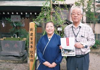 記念樹として植えたしだれ桜の前で記念誌を持つ黒木亀宮司とセツ子さん