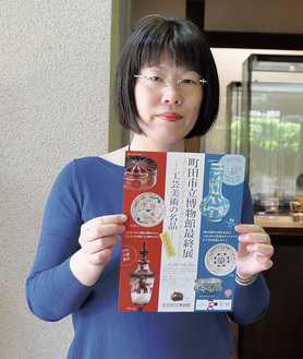 チラシを持つ学芸員の齊藤晴子さん