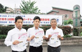 会場のJA町田市堺支店前でチラシを掲げる実行委員メンバー