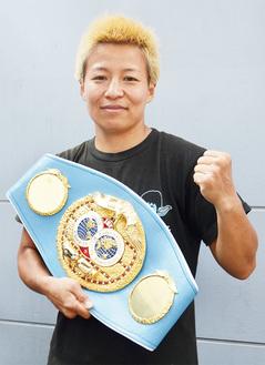 ずっしり重いチャンピオンベルトを手にガッツポーズを決める世界王者
