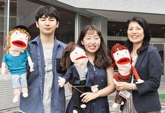 MVに登場した手作り人形を掲げる斎藤さん、澁谷さん、杉森教授(左から)