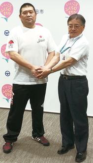 表敬訪問時に石阪市長と握手を交わす石川さん(写真左)