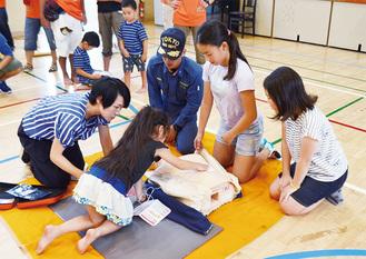 AEDの使用方法を教わりながら心肺蘇生法を体験する子どもたち