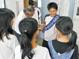 応援メッセージ付きのタスキを受け取る鹿沼さん(3日、藤の台小学校)
