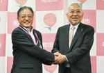 握手する祇園会長(右)と石阪丈一市長