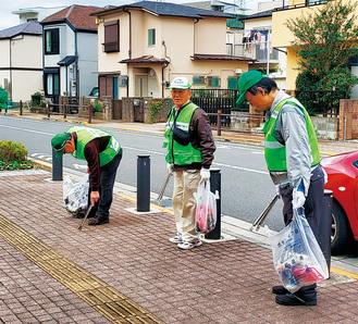 ゴミ袋を手に市役所前の歩道を丁寧に清掃