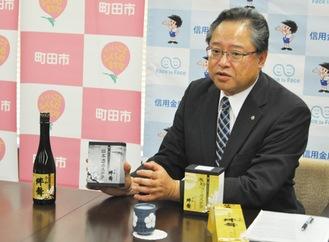 ネットワークにより商品化された酒やカステラを紹介する川本理事長