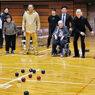 エキシビジョンで真島さん(右)の投げた球の行方を追う松平さん(左から2人目)