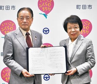 協定書を掲げる山本学長(右)と石阪市長
