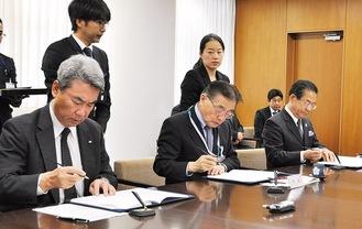 協定書に署名する石阪市長ら