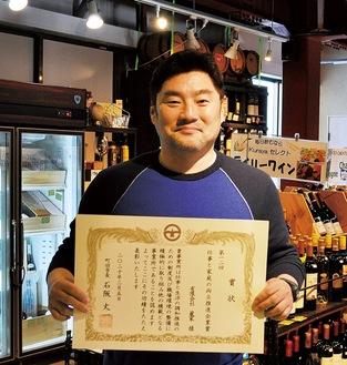 賞状を掲げる浅沼芳征代表取締役