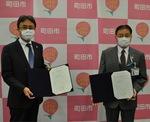 覚書を掲げる林会長(左)と石阪市長