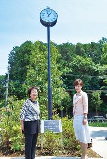 時計塔の前に立つ前田会長(左)と柴崎次期会長