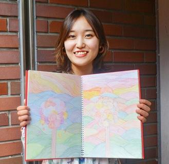 受賞作の原画を手に笑顔を見せる小林さん