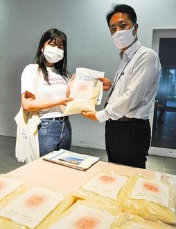 JA町田市の庄司さん(右)から学生にお米が手渡された