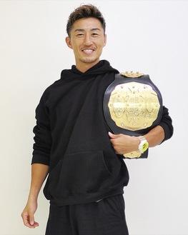 チャンピオンベルトを肩に掛け笑顔の山崎選手