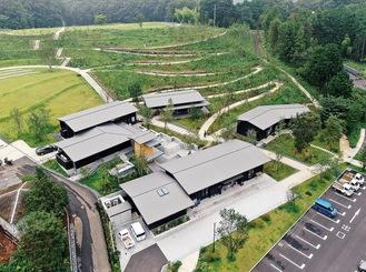 拠点となる建物の奥には広い緑の空間が広がる