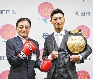 石阪市長と一緒にポーズを取る山崎選手(右)
