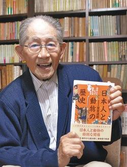 膨大な蔵書を背に新書を手にする實吉達郎氏