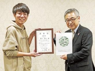 最優秀賞を受賞した新井さん(左)とロゴを持つ竹島代表