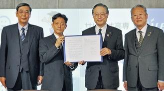協定書を手にする小島校長(中央左)と川本理事長(中央右)
