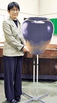 実寸大パネルで壺を紹介する矢島副館長