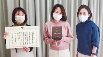 表彰状と楯を手にする女性職員3人