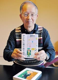 著書を手にする佐藤さん。孫が描いたイラストが表紙を飾る