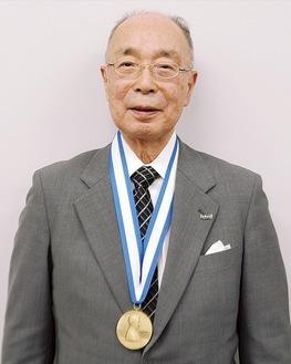 メダルを首からかけてほほ笑む伊賀氏