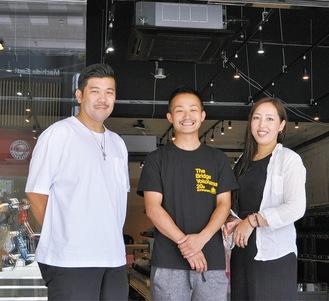 新装中の店舗前で若月社長夫妻とHIPHOP歌手の野武士(中央)