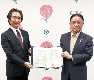 協定書を取り交わした水谷店長(左)と石阪市長
