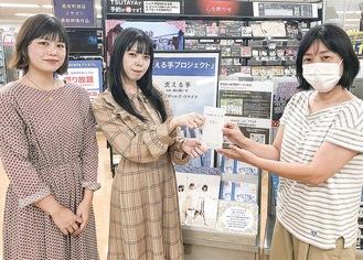 田中さん(右)へ収益を届けた町ガの2人