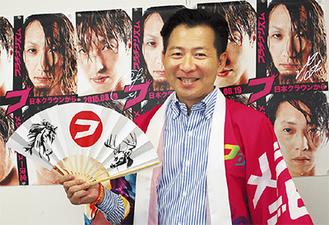 フラチナリズムのポスターの前で、フラチナのはっぴを羽織り、フラチナの扇子をもつ岡田さん