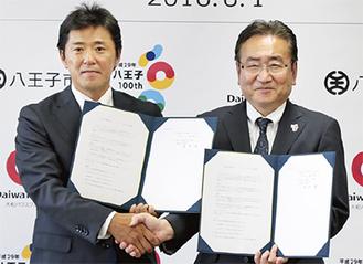 調印式で石森孝志市長と握手を交わす萩原支店長(左)