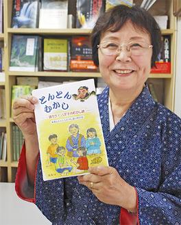 語る時にまとう作務衣姿で初の書籍を持つ吉田さん